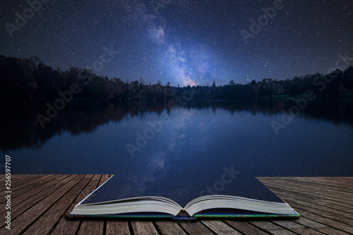 Foto auf AluDibond Blaue Nacht Vibrant Milky Way composite image over landscape of still lake coming out of pages in magical story book