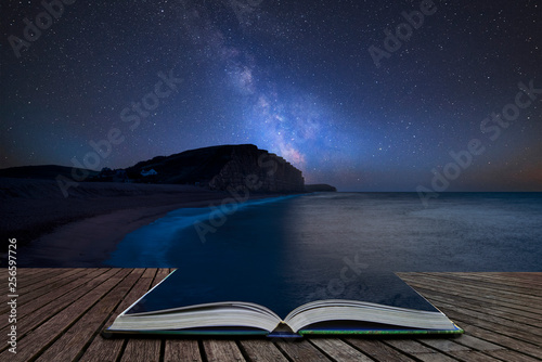 Spoed Foto op Canvas Nachtblauw Vibrant Milky Way composite image over landscape of long exposure of West Bay in Dorset coming out of pages in magical story book