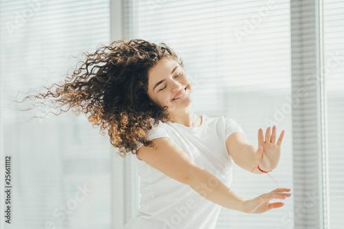 The beautiful woman listening the music near the window - 256611112
