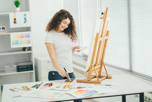 The Cute Woman With An Art Brush Painting A Picture On The Easel