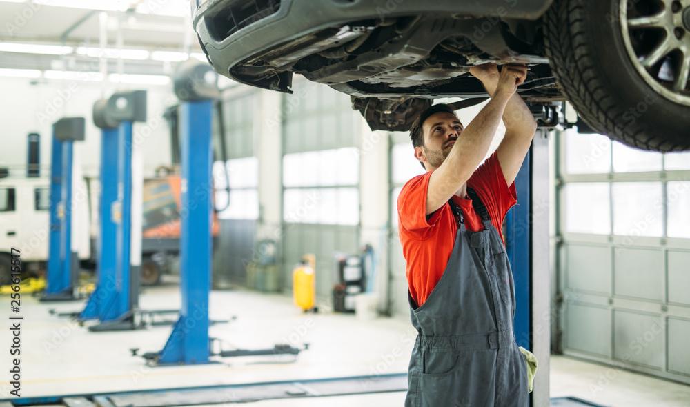 Fototapety, obrazy: Car mechanic working at automotive service center