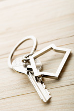 House Key With A Keychain On Wooden Desk Concept For Real Estate