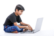 Cute Little Indian/Asian Boy Studying Or Playing Game With Laptop Computer
