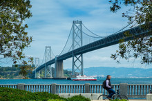 San Francisco Bay Bridge With Blurry Man Riding Bicycle During Day Time