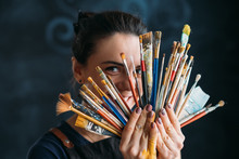 Artist And Art Supplies. Tools For Talent. Smiling Woman Painter In Apron Posing With Paintbrushes Bunch.