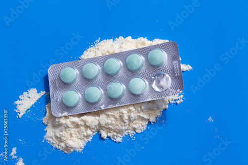 Fotografía  Protein powder in measuring plastic spoon and vitamin complex, omega 3, glucosamine capsules, supplements on blue background, sports nutrition, top view