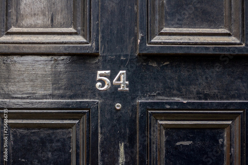 Fotografía  House number 54 with the fifty-four in silver numbers screwed to a black wooden