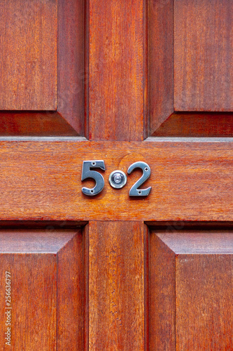 Photo  House number fifty-two on a red wooden door with natural grain with the 52 in si
