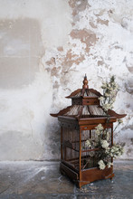 Chinese Old Wooden Bird Cage, Used As Decoration With Flower Inside, On The Floor And Cement Wall Background