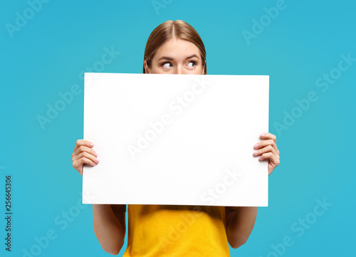 Photo  Funny girl with white empty poster, looking away, on blue background