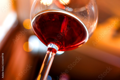 Glass of red wine detail with blurry background closeup - 256649718
