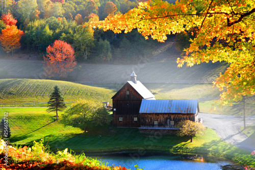 Fotografía  Old barn in Vermont rural side surrounded by fall foliage