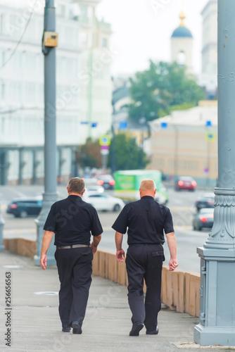 Men police in uniform walking around the city Canvas Print