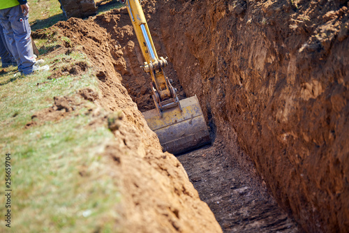 Photo Backhoe - Digging a Trench Excavator digs the foundation for water pipes
