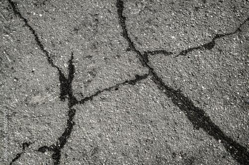 Fotografía  Old road background surface of gray cracked asphalt texture closeup