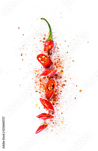 Red chili pepper, cut into pieces and isolated on white background. Hot spice, red chili pepper and chili powder.  Fototapete