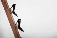 Female Shoes On Wooden Ladder Against Light Background. Concept Of Career Failure
