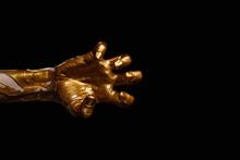 Female Hand With Golden Paint Against Dark Background