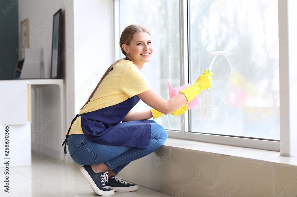 Fototapeta Beautiful woman cleaning window at home