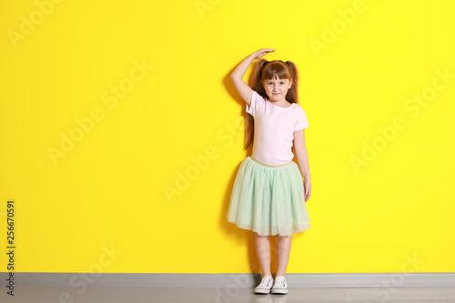 Fotografía  Cute little girl measuring height near color wall