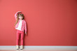 Cute little girl measuring height near color wall