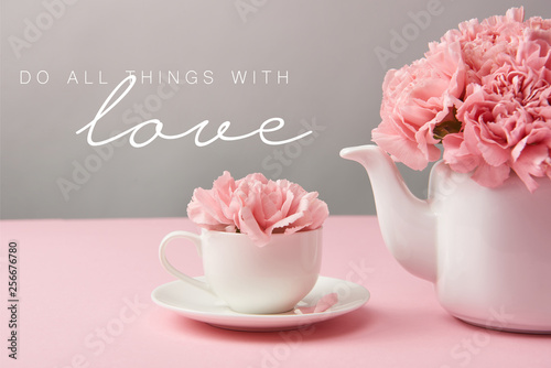 Obraz na plátně pink carnation flowers in cup and teapot on grey background with do all things w