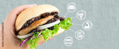 Crickets insect for eating as food items made of cooked insect in burger and vegetable on woman's hand with media icons nutrition for fast food, is good source of protein edible Poster Mural XXL