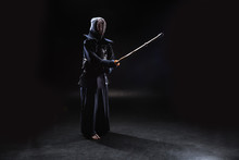 Full Length View Of Kendo Fighter In Armor Practicing With Bamboo Sword On Black