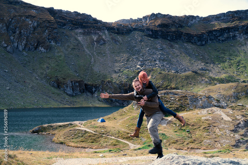 Happy couple having fun with raised arms on mountain top. Space for text, hiking travel camping vacation. Transfagarasan Romania, Balea Lac