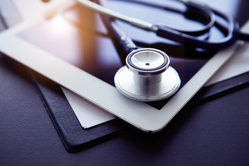 Close up of stethoscope and tablet on table. Medicine and technology concept