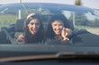 Two beautiful young women driving in a convertible pointing at the camera