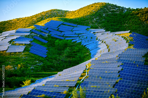 Cuadros en Lienzo Building a solar photovoltaic panel on a hillside under the setting sun