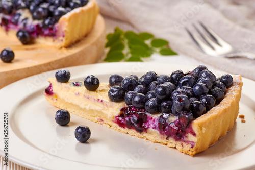 Photo  Piece of  custard tart with blueberries on dish