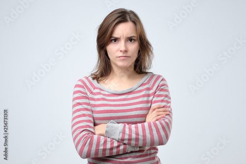 Young serious european woman portrait looking with irritation at camera.