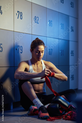 Fotografie, Obraz  Muscular build woman wrapping hands with a bandage before boxing training
