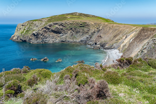 фотография A bay of clear blue water with a small rocky beach
