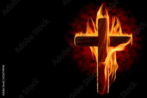 Obraz Cross burning or lighting concept theme with wooden crucifix engulfed in fiery flames isolated on black background with copy space. It was used as a declaration of war, to protest, to intimidate, etc - fototapety do salonu