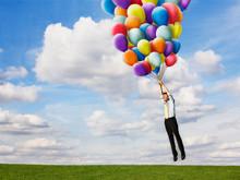 Businessman Taking Off Holding Helium Balloons
