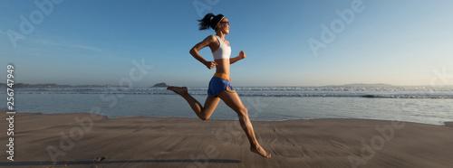 Fototapeta young fitness woman running at sunrise beach obraz