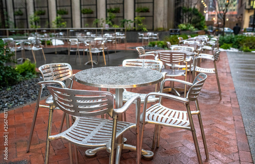 Empty dining tables and chairs in a street cafe after the rain