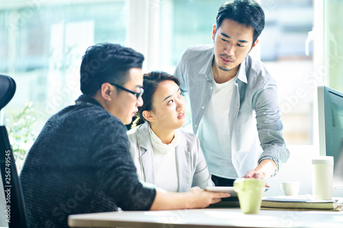 Fototapeta three young asian entrepreneurs discussing business in office obraz na płótnie