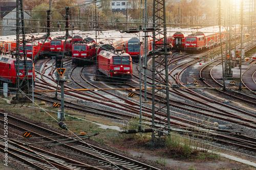 Obraz Bahn - Züge fahren am Bahnhof über Schienen entlang  - fototapety do salonu
