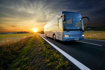 Bus traveling on the asphalt road in rural landscape at sunset