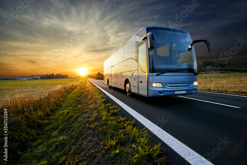 Foto  Bus traveling on the asphalt road in rural landscape at sunset