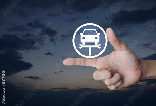 Fotografía  Hand pressing service fix car with wrench tool flat icon over sunset sky, Busine