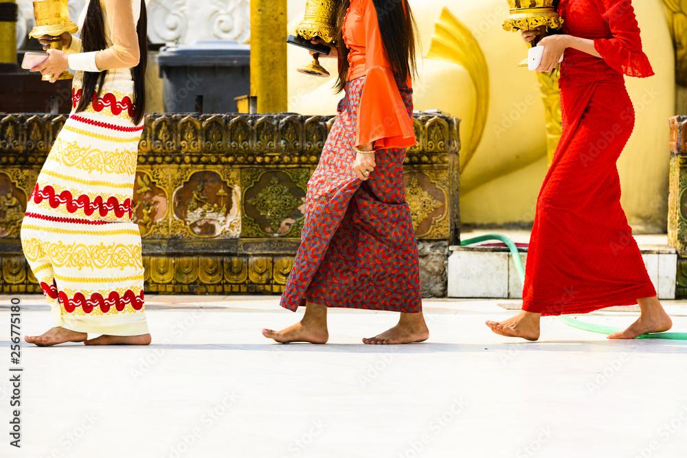 Fototapeta (selective focus) Some Burmese Buddhist faithful are walking barefoot around the Shwedagon Pagoda wearing a traditional and colorful Longyi (traditional Burmese clothes). Yangon, Myanmar.
