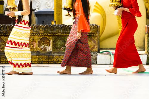 Obraz (selective focus) Some Burmese Buddhist faithful are walking barefoot around the Shwedagon Pagoda wearing a traditional and colorful Longyi (traditional Burmese clothes). Yangon, Myanmar. - fototapety do salonu