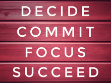 Motivational And Inspirational Words - Decide, Commit, Focus,Succeed Written On Maroon Background.