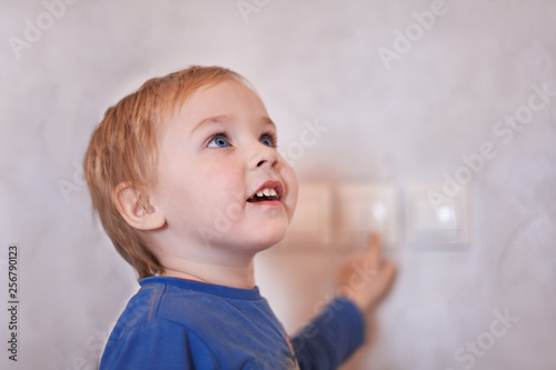 7f2783a68 Pretty blonde caucasian baby boy turns on/off the light-switch ...