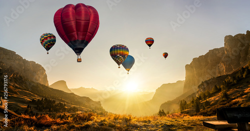Foto op Plexiglas Oranje Beautiful panoramic nature landscape of countryside mountains with colorful high hot air balloons festival in summer sky. Vacation travel panorama background.